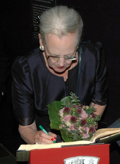 Billede af dronningen, der skriver i gæstebog på H. C. Andersens Hus