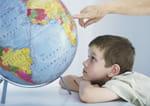 Dreng der kigger på en globus