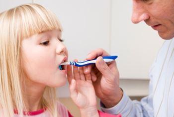 Far børster tænder på pige