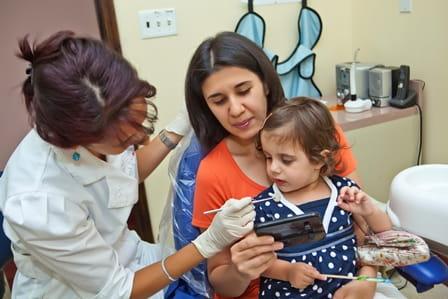 Barn sidder med forældre i tandlægestolen