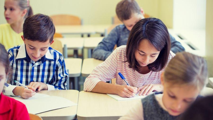 Skolebørn der sidder i klasseværelse