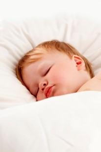 Lille dreng der sover i hvidt sengetøj